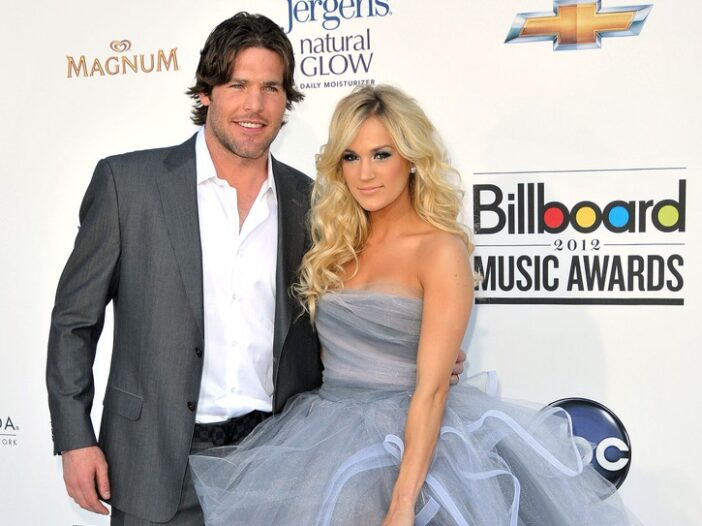 Mike Fisher, in a gray suit, stands with Carrie Underwood, in a gray and blue dress