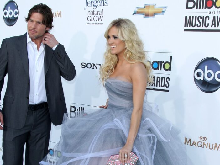 Mike Fisher, wearing a dark suit, stands near Carrie Underwood at the Billboard Music Awards