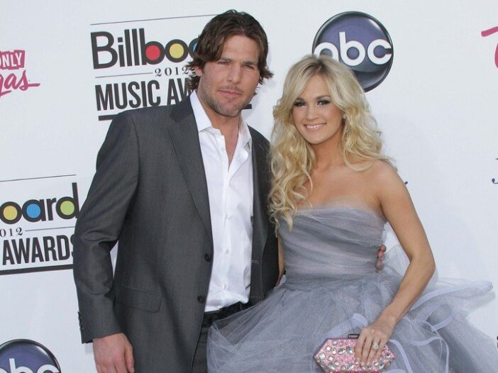 Mike Fisher wearing a gray suit standing on the red carpet with Carrie Underwood, in a gray dress