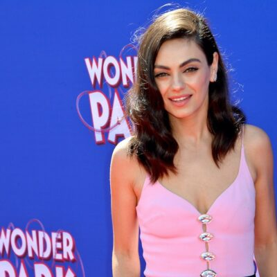 Mila Kunis smiling in a pink top against a blue background