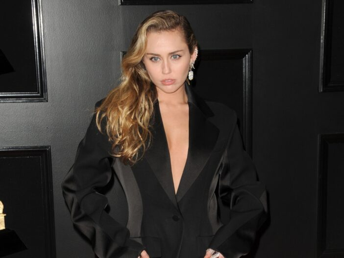 Miley Cyrus in a low cut black outfit, looking serious.