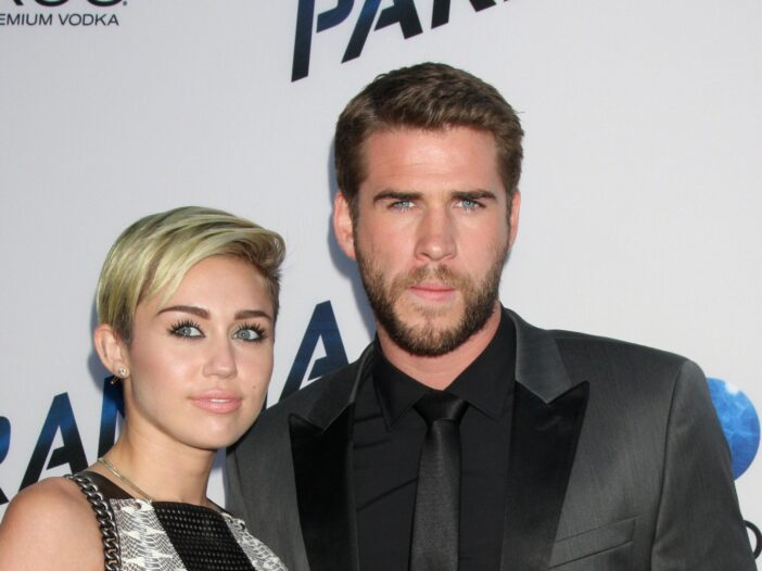 Miley Cyrus on the left, Liam Hemsworth on the right, together at a red carpet event.