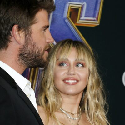 Miley Cyrus on the right, looking up and smiling at Liam Hemsworth, in profile.