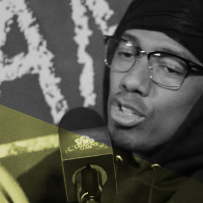Nick Cannon wearing glasses and a hoodie while hosting his podcast
