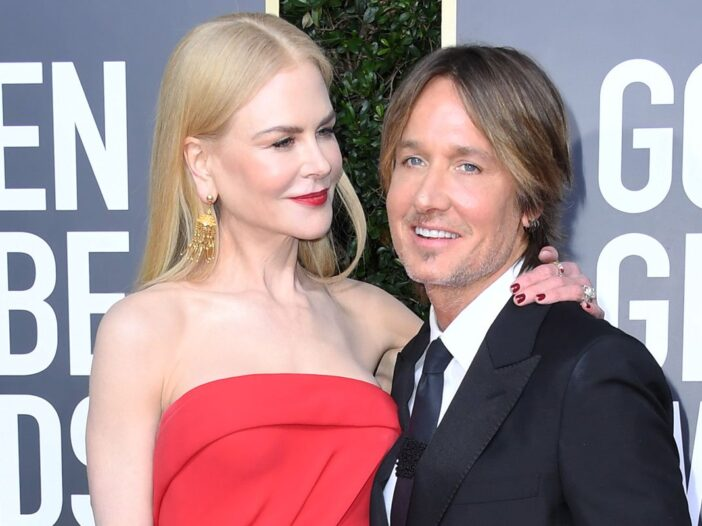 Nicole Kidman looking and smiling at Keith Urban on the red carpet at the Golden Globes.