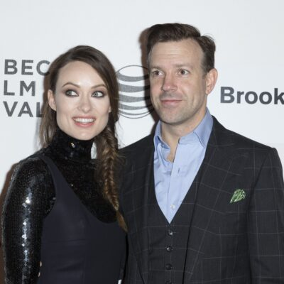 Olivia Wilde and Jason Sudeikis, both dressed in black, pose before a white background