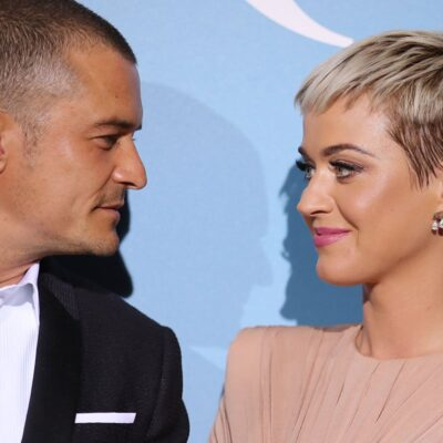 Orlando Bloom and Katy Perry smiling at each other.