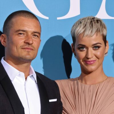 Orlando Bloom slightly smiling in a suit next to Katy Perry smiling in a peach colored dress against