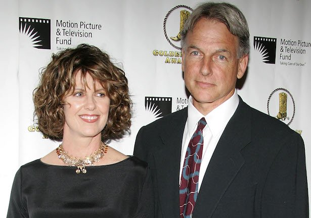 Pam Dawber in a black top next to Mark Harmon in a black suit, white shirt, patterned red tie