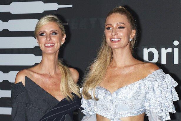 Paris Hilton in a white frilly dress smiles next to Nicky Hilton in a dark grey-black dress