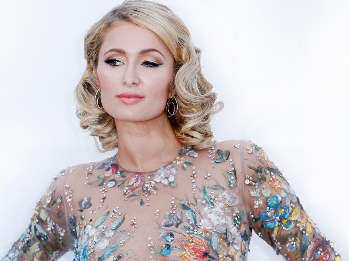 Paris Hilton looking coy, wearing a floral patterned dress in front of a white background.