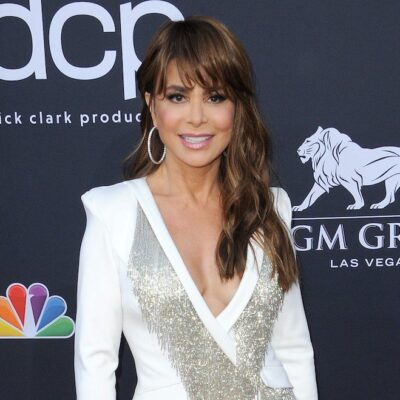 Paula Abdul smiling in a white blouse against a black background