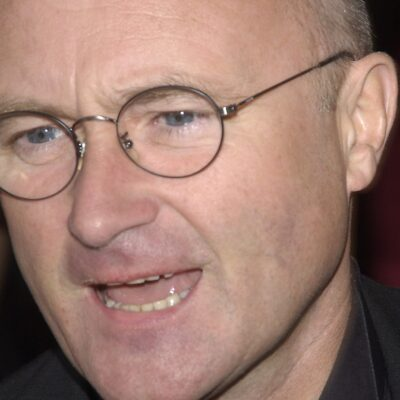 Phil Collins wearing a black suit on the Academy Awards red carpet