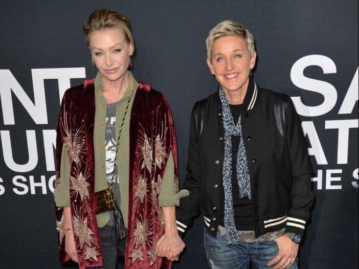 Portia de Rossi and Ellen DeGeneres stand hand in hand on the red carpet