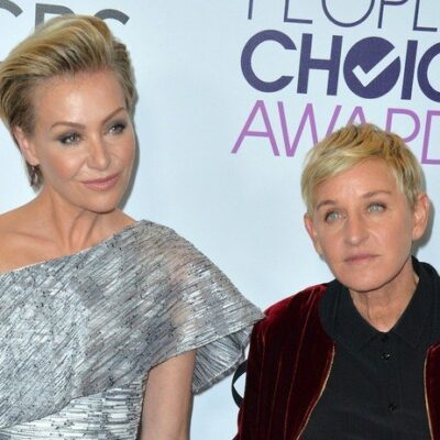 Portia de Rossi on the left in a grey and white dress, Ellen DeGeneres on the right in a black shirt and red jacket.