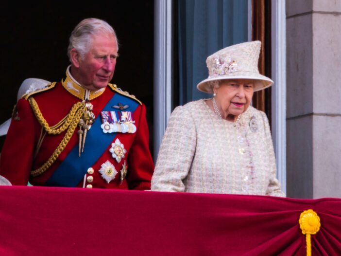 Prince Charles in a ceremonial military uniform standing on a balcony at Buckingham Palace with Queen Elizabeth.