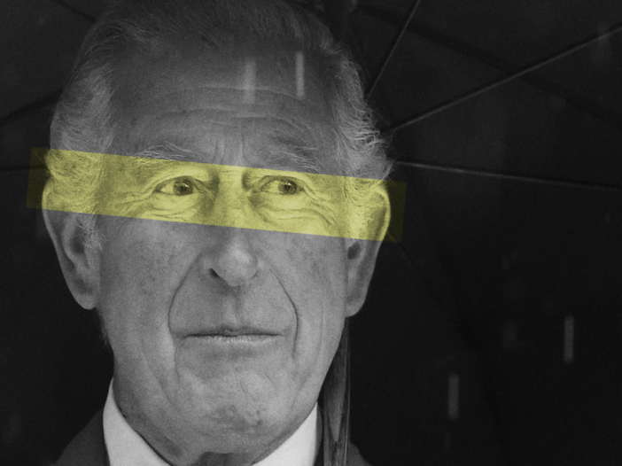 Prince Charles wearing a dark suit and standing beneath an umbrella in the rain