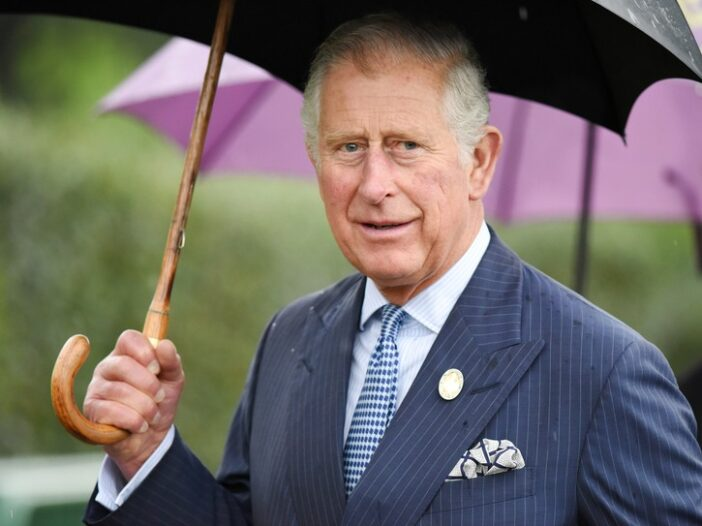 Prince Charles wearing a pinstriped suit and carrying an umbrella during a light rain