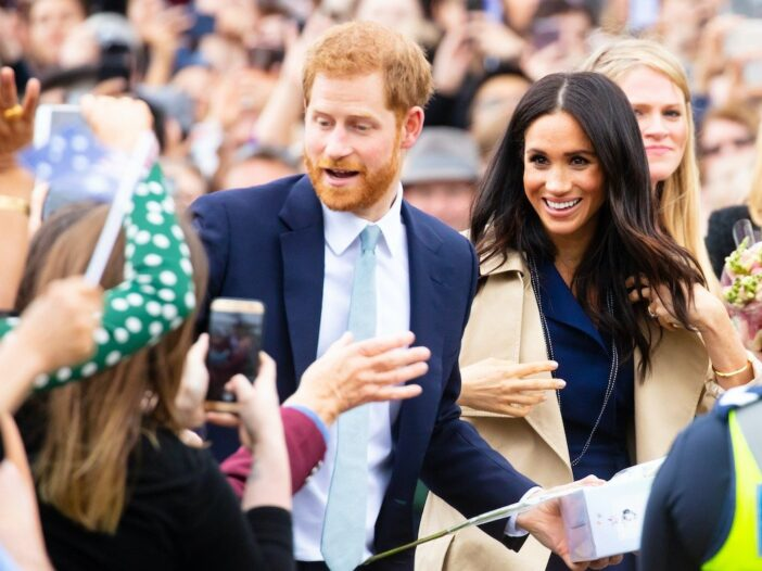 Prince Harry in a blue suit smiling in a crowd with wife Meghan Markle in a khaki jacket