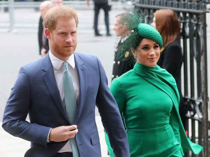 Prince Harry in a suit and Meghan Markle in a green dress and hat.