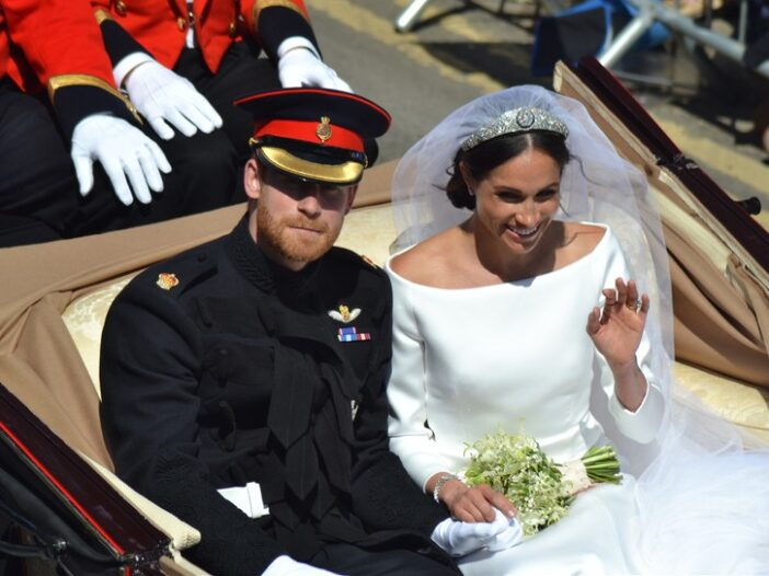 Prince Harry in his military dress sitting with Meghan Markle in a carriage after getting married