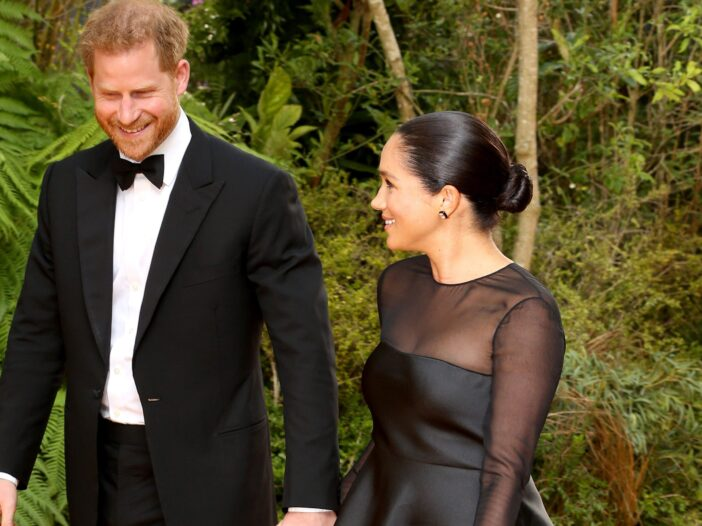 Prince Harry in the left in a tux, holding hands with Meghan Markle in a black formal dress.