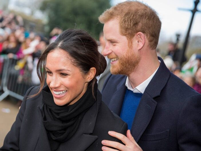 Prince Harry standing behind Meghan Markle with his hand on her shoulder.
