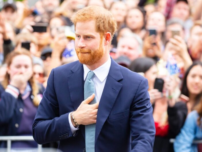 Prince Harry wearing a blue suit, greeting a crowd.