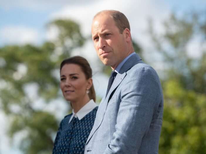 Prince William in a grey suit looks to his left standing in front of Kate Middleton in a blue patter