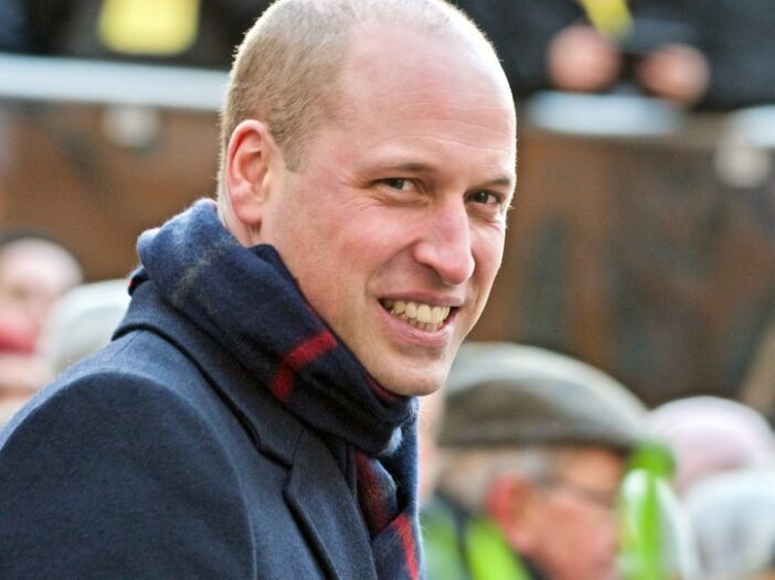 Prince William smiling in a grey coat and patterned scarf outdoors