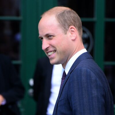 Prince William smiling in a navy suit and purple tie outside
