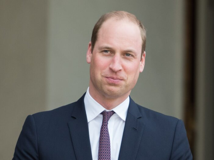 Prince William wearing a blue suit and purple tie.
