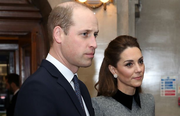 Prince William wearing a dark suit standing next to Kate Middleton, who is wearing a gray and black