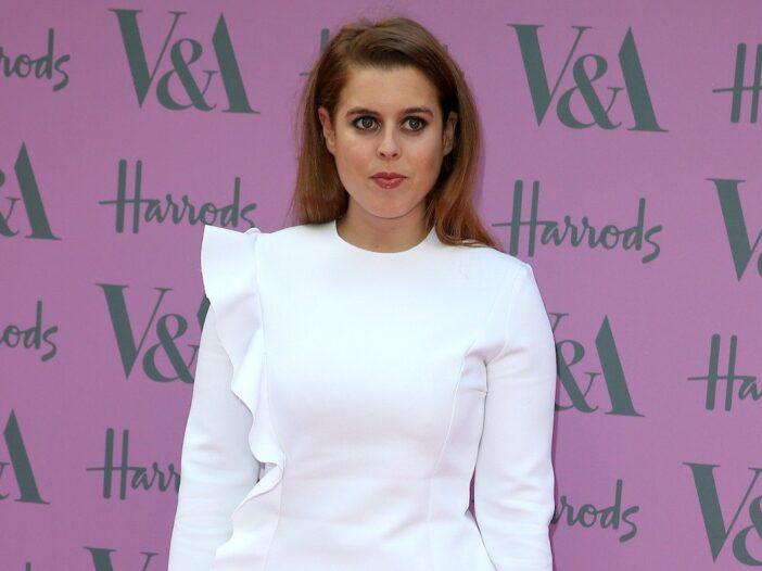 Princess Beatrice smiling in a white dress against a pink background