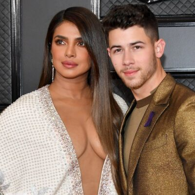 Priyanka Chopra in a white dress looks to her right with Nick Jonas in a brown suit smiling at the c