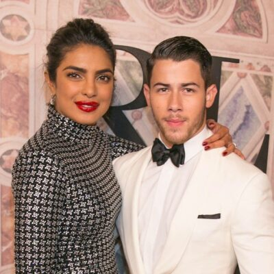 Priyanka Chopra smiling in a black and silver dress with Nick Jonas in a white tux