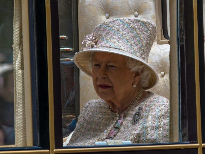 Queen Elizabeth grimacing looking out of a carriage window in a white, pink, and blue outfit