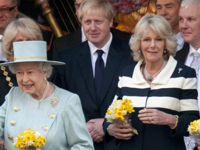 Queen Elizabeth II in a light blue outfit, with her back to Camilla Parker Bowles in a striped shirt. Boris Johnson lurks in the background.