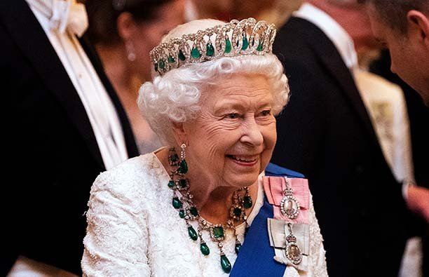 Queen Elizabeth II wearing a white dress and a tiara at an official event