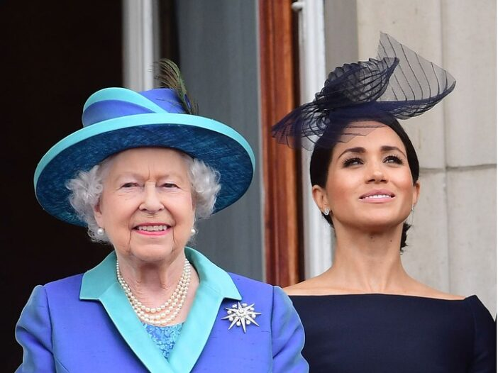 Queen Elizabeth on the left in a light blue dress and hat, Meghan Markle on the right in a dark blue dress and hat