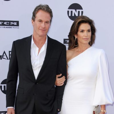 Rande Gerber wearing a black suit and posing with wife Cindy Crawford, in a white dress
