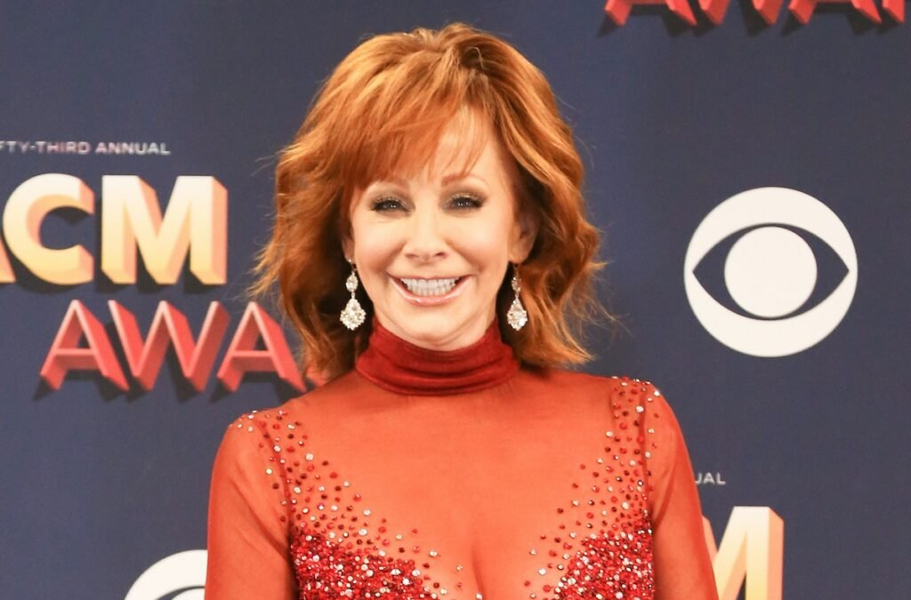 Reba McEntire smiling in a red dress