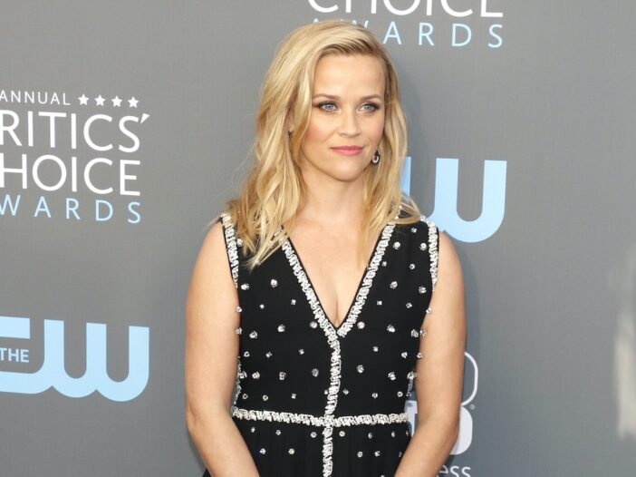Reese Witherspoon posing in a black and silver dress on a red carpet