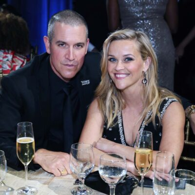 Reese Witherspoon smiles in a black dress sitting with husband Jim Toth in a black suit