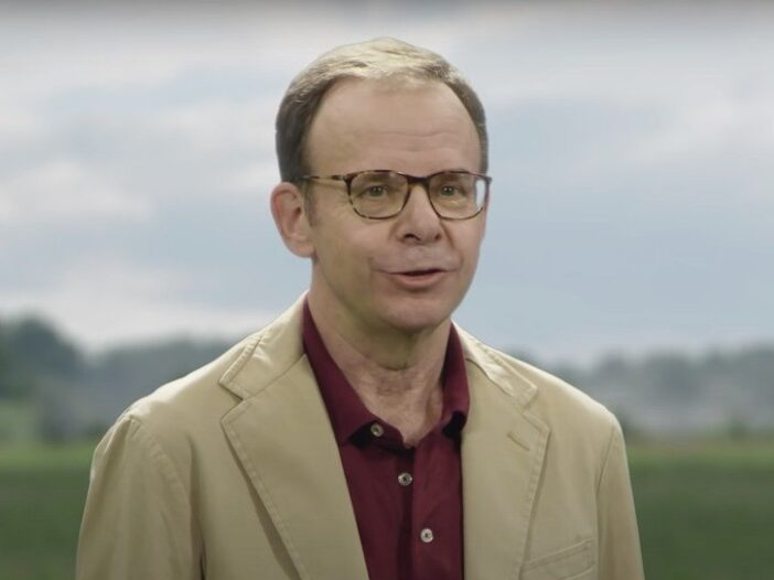 Rick Moranis wearing a tan blazer during a Mint Mobile commercial