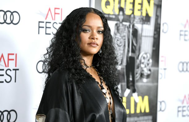 Rihanna in a black, silky wrap dress on the red carpet.