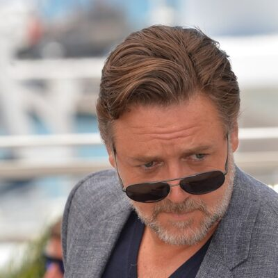 Russell Crowe looking over the top of a pair of sunglasses pushed down on his nose.