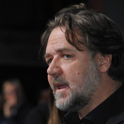 Russell Crowe wearing a black button-down shirt at a red carpet event.