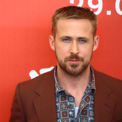 Ryan Gosling in a pattern shirt and reddish-colored jacket.