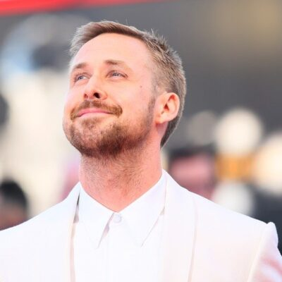 Ryan Gosling looking up and smiling in a white suit.